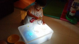 Scooping the water beads out of the containers onto the light box!